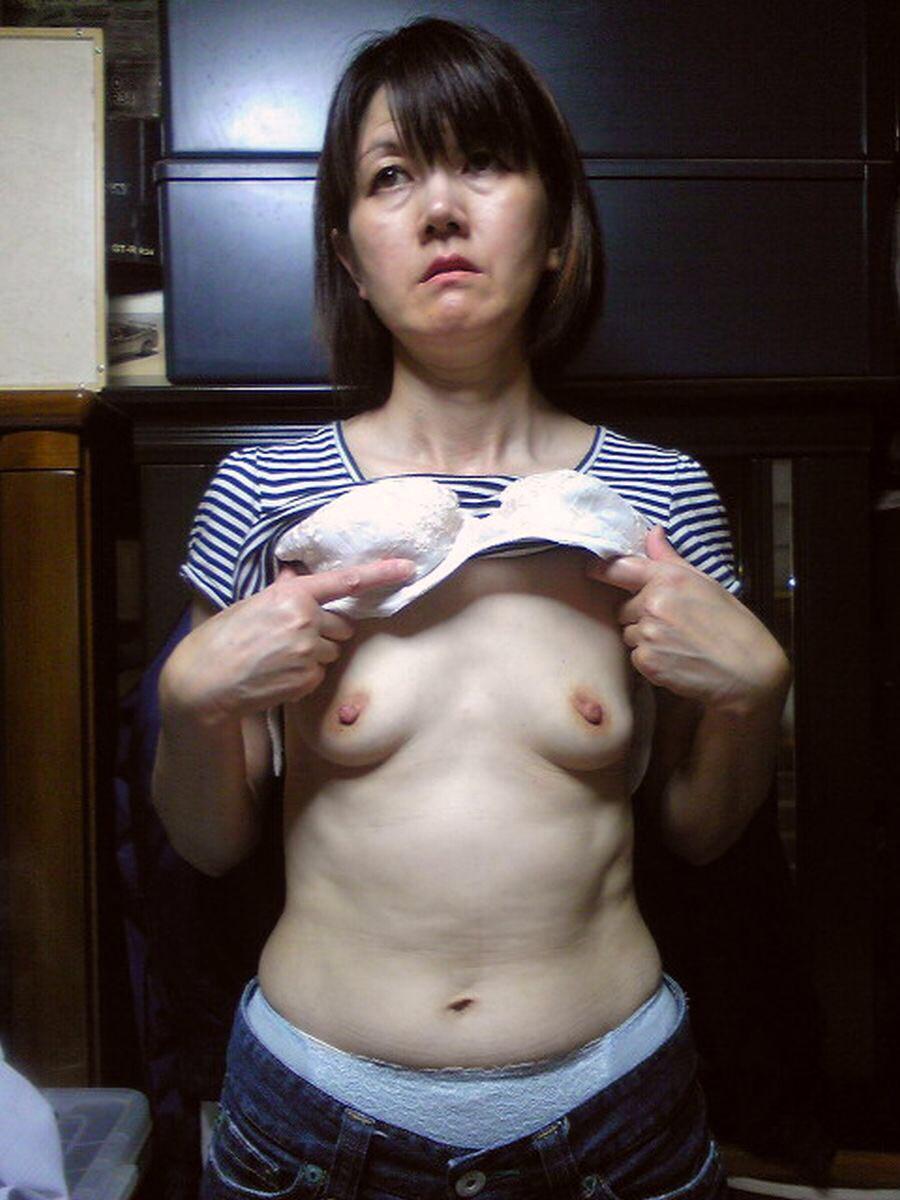 服とブラをたくし上げ貧乳を見せつける人妻!