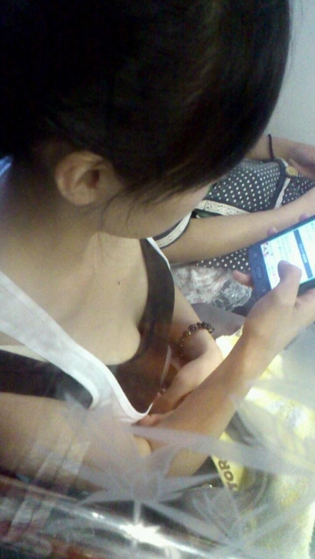 電車内にいたスマホに夢中の女性の胸チラ!