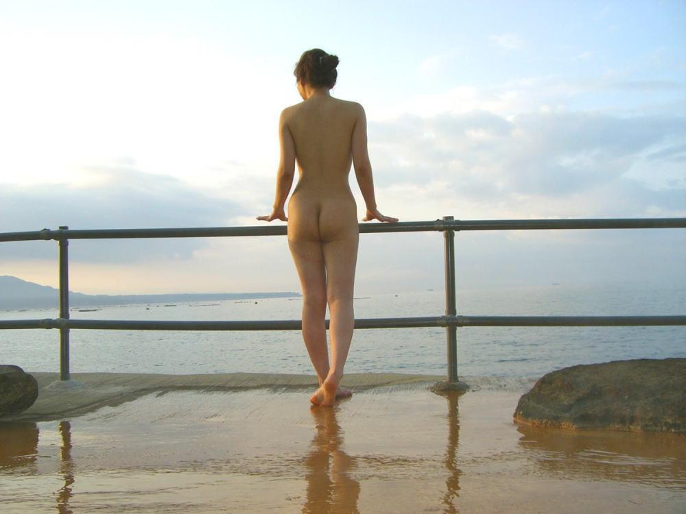 海を眺めている全裸女性のお尻!
